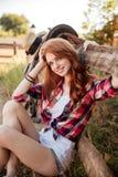 Rozochocony śliczny młodej kobiety cowgirl jest usytuowanym na gospodarstwie rolnym Zdjęcie Royalty Free
