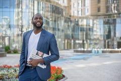 Rozochocony Afrykański męski pracownik z gazetą Fotografia Stock