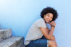Rozochocony amerykanina afrykańskiego pochodzenia mężczyzna z afro obsiadaniem na krokach Fotografia Stock