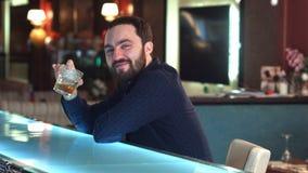 Rozochocony atrakcyjny młody człowiek pije wewnątrz w spojrzeniu przy kamery ono uśmiecha się i barze Zdjęcia Stock