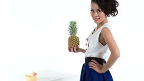 Rozochocony azjata model z ananasem i żółtą kaczką pozuje w studiu zbiory