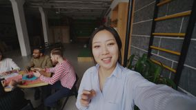 Rozochocony azjatykci kobiety mienia smartphone i onlive wideo wezwanie w nowożytnym biurze podczas gdy jej koledzy pracuje zbiory wideo