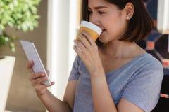 Rozochocony azjatykci młodej kobiety obsiadanie w kawiarni pić kawowy i używać smartphone dla opowiadać, czytać i texting, obrazy royalty free