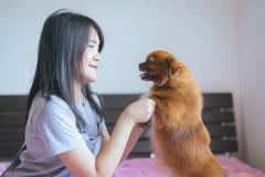 Rozochocony azjatykci młody nastoletni dziewczyny bawić się w domu i szczęśliwa zabawa z jej psem Fotografia Royalty Free