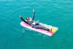 Rozochocony bizneswoman na basen tratwie z laptopem zdjęcia stock