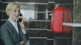 Rozochocony bizneswoman opowiada z personelem z depeszującym czerwonym telaphone przy przyjęciem w hotelu lobby Biznes, podróż i zbiory