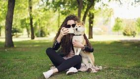 Rozochocony blogger zwierzęcia domowego właściciel bierze selfie z jej psim używa smartphone, istota ludzka i zwierzę siedzi na g zbiory wideo