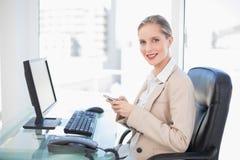 Rozochocony blondynka bizneswomanu wysylanie sms obraz stock
