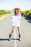 Rozochocony blondynki mienia znak podczas gdy hitchhiking na drodze Zdjęcie Stock