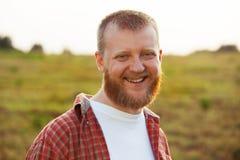 Rozochocony, brodaty mężczyzna w czerwonej koszula, zdjęcie royalty free
