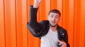 Rozochocony caucasian mężczyzna z brodą rzuca pieniędzy dolary w kamerę, pomarańczowy tło, zwolnione tempo zbiory wideo