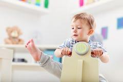 Rozochocony chłopiec chlanie na kołysa krześle w formie hulajnoga obrazy royalty free