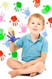 Rozochocony chłopiec obsiadanie z ręką malującą Zdjęcia Royalty Free