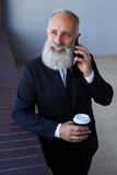 Rozochocony dżentelmen opowiada na telefonie podczas gdy trzymający filiżankę kawy Fotografia Royalty Free