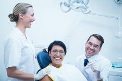 Rozochocony dentysta i asystent z żeńskim pacjentem Zdjęcia Stock