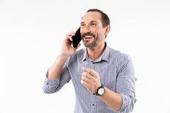 Rozochocony dorosły mężczyzna opowiada telefonem komórkowym obrazy stock