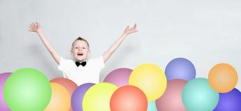 Rozochocony dzieciak skacze out od kolorowych balonów Obrazy Stock