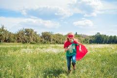 rozochocony dzieciak w czerwonym bohater maski i przylądka bieg w łące obraz stock