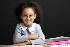 Rozochocony dzieciak z długim falistym puszystym czarni włosy obsiadaniem w sala lekcyjnej obrazy stock