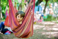 Rozochocony dziecko bawić się i kłama wśrodku hamaka zdjęcie stock