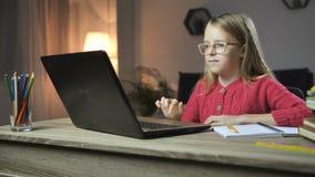 Rozochocony dziecko robi pracie domowej z laptopem online zbiory