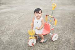 Rozochocony dziecko stojak na dzieciaka ` s bicyklu i przyglądającej kamerze na betonowej drogi tle Obrazy Stock