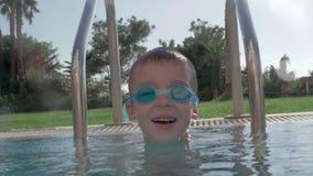 Rozochocony dziecko w gogle kąpać się w plenerowym pływackim basenie zbiory wideo