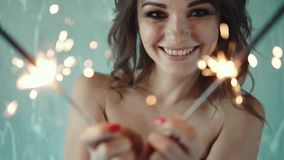 Rozochocony dziewczyny mienie w rękach sparklers i śmiać się młoda kobieta przy przyjęciem Świąteczny nastrój Sens zbiory