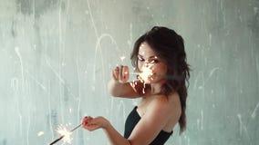 Rozochocony dziewczyny mienie w rękach sparklers i śmiać się młoda kobieta przy przyjęciem Świąteczny nastrój wolny zbiory