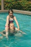 Rozochocony dziewczyny obsiadanie na ona ojcowie brać na swoje barki w basenie fotografia stock