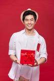 Rozochocony elegancki azjatykci młody męski mężczyzna trzyma prezent dalej Obraz Stock