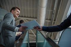 Rozochocony facet trzyma kontraktacyjny na eskalatorze wraz z coworker Fotografia Royalty Free