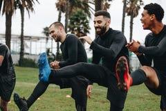 Rozochocony gracz futbolu robić grże w górę ćwiczeń na polu przed dopasowaniem Szczęśliwi futboliści robi nodze podnoszą pozycję  zdjęcie stock