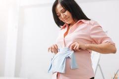 Rozochocony kobieta w ciąży mienia dziecko odziewa Obraz Stock
