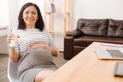 Rozochocony kobieta w ciąży pije mleko Obrazy Stock
