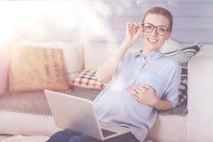 Rozochocony kobieta w ciąży siedzi blisko kanapy fotografia royalty free