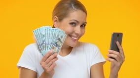Rozochocony kobiety mienia smartphone i wiązka dolary, online bankowość usługa zdjęcie wideo