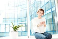 Rozochocony kobiety obsiadanie na windowsill w biurze i używać smartphone obraz stock