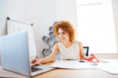 Rozochocony kobiety rozcięcia kolor papierowy i używa laptop w biurze zdjęcia stock