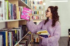 Rozochocony młodej dziewczyny kładzenia puszek czytający menchii książkę zdjęcia stock