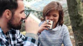 Rozochocony mężczyzna i nastoletni chłopak pije herbaty podczas wiosny wycieczkować zbiory wideo