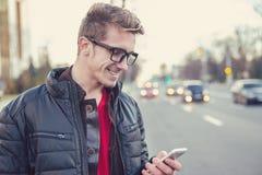 Rozochocony mężczyzna używa telefon komórkowego outdoors zdjęcia royalty free