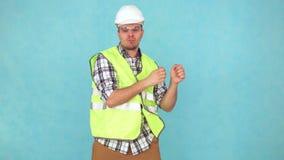 Rozochocony mężczyzna w budowa mundurze i białym hełmie tanczy, zdjęcie wideo