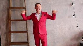 Rozochocony mężczyzna w czerwonym kostiumu tanczy zdjęcie wideo