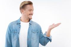 Rozochocony mężczyzna wskazywać z ukosa i patrzeć jego rękę Zdjęcie Stock
