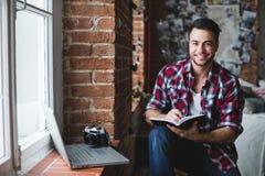 Rozochocony mężczyzna z laptopem pisze w notatniku zdjęcia royalty free