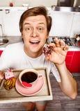 Rozochocony mężczyzna z ranków ciastkami i kawą zdjęcia royalty free