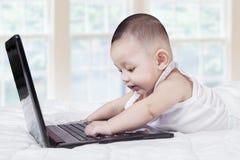 Rozochocony męski dziecko pisać na maszynie na laptopie Fotografia Royalty Free