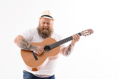 Rozochocony męski fatso bawić się gitarę Fotografia Stock