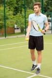 Rozochocony męski gracz w tenisa przygotowywający dla gry Obrazy Stock